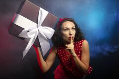 Woman holding a gift and brings her finger to her lips Photo in studio, dark background