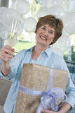 Woman Holding Gift And Champagne Flute At Party Stock Images