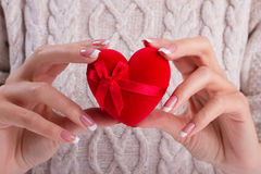 Woman holding a gift in the form of heart. Royalty Free Stock Photos