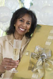 Woman Holding Gift And Glass Of Champagne Royalty Free Stock Images