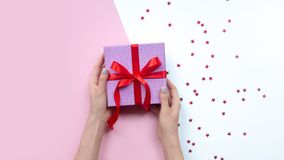 Woman holding gift in hands. Pink gift box. Copy space stock photos