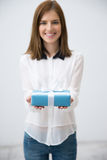 Woman holding gift over gray background Stock Image