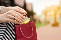 A woman is holding a gift package bag in hand shopping jewerly box ring. On blur nature sun background stock photo