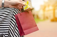 A woman is holding a gift package bag in hand shopping jewerly box ring. On blur nature sun background stock photography
