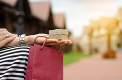 A woman is holding a gift package bag in hand shopping jewerly box ring. On blur nature sun background stock image