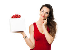 Woman holding gift and thinking Stock Image