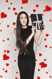 Woman holding gift. Young beautiful woman with long hair wearing black cocktail dress is holding elegantly wrapped gift. Woman wondering whats inside the box Royalty Free Stock Photography