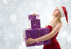 Woman holding gifts wearing Santa costume Stock Photography