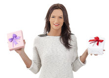 Woman Holding Gifts. Young smiling woman holding two gift boxes, isolated against a white background Royalty Free Stock Photography