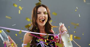 Woman holding a glass and a bottle of champagne 4k. Digital composite of a Caucasian woman holding a glass and a bottle of champagne dancing and celebrating stock video footage