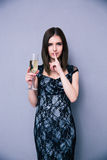 Woman holding glass of champagne with finger over lips Royalty Free Stock Photos