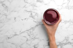 Woman holding glass with fresh beet juice. On marble table, top view royalty free stock image