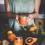 Woman holding glass of fresh blood orange juice, square crop royalty free stock photo