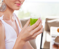 Woman holding glass of a green juice in her hand hand Stock Images