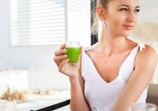 Woman holding glass of a green juice in her hand Royalty Free Stock Photography