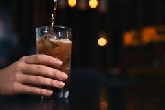 Woman holding glass with ice cubes while pouring cola at table indoors, closeup. Space for text royalty free stock images