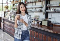 Woman holding glass of iced chocolate milk in a cafe. Young woman holding glass of iced chocolate milk in a cafe royalty free stock images