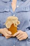 Woman holding glass jar of honey Royalty Free Stock Photo