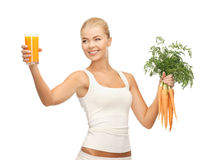 Woman holding glass of juice and carrots Royalty Free Stock Photos