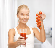 Woman holding glass of juice and tomatoes Stock Photography