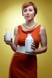 Woman holding glass of milk and bottle Royalty Free Stock Photos