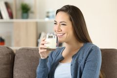 Woman holding a glass of milk on a couch Royalty Free Stock Images