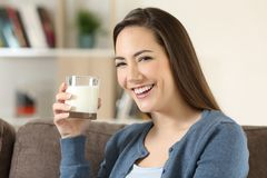 Woman holding a glass of milk looking at camera. Portrait of a happy woman holding a glass of milk looking at camera sitting on a couch in the living room at Stock Photo