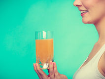 Woman holding glass of orange flavored drink Stock Image