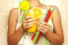 Woman holding a glass of orange juice and drinking straws Royalty Free Stock Photography