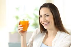 Woman holding a glass of orange juice looking at you Royalty Free Stock Photography