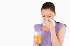 Woman holding a glass of orange juice and sneezing Stock Images