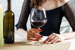 Woman holding a glass of red blue waiting for man stock images
