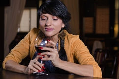 Woman holding a glass of red wine at the bar Stock Photography