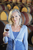 Woman Holding Glass Of Red Wine In Cellar Royalty Free Stock Image