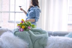 A woman is holding a glass of red wine and a fresh bouquet of yellow and pink tulips. Spring flowers. In a cozy house, by the stock photo