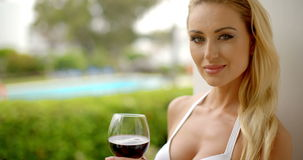 Woman Holding Glass of Red Wine Outdoors near Pool. Attractive Blond Woman Wearing White Bikini Holding Glass of Red Wine Outdoors near Swimming Pool Smiling and stock video