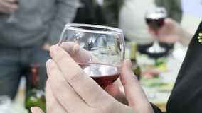 Woman holding a glass of red wine. People clink glasses with drinks at the event. Footage 4K, Ultra HD, UHD.  stock footage