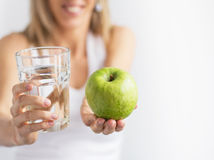 Woman holding glass of water and green apple. Stock Images