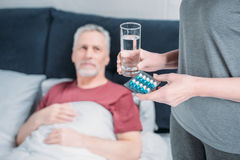 Woman holding glass of water and medicines for sick husband royalty free stock photography