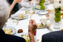 Woman holding a glass of wine, feast stock photography