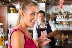 Woman holding a glass of wine in hand at the bar royalty free stock photo