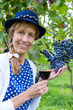 Woman holding glass of wine near bunch of blue grapes Stock Photography