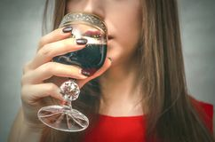 Woman drinking wine from wineglass. Woman is holding a glass of wine and taste it. Wine degustation Stock Photo