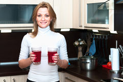 Woman holding glasses with lemonade. Beautiful happy smiling female in kitchen interior. One person only Stock Images
