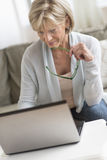 Woman Holding Glasses While Using Laptop Royalty Free Stock Photos