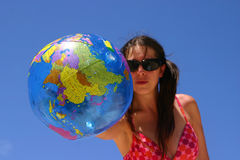 Woman holding a globe. A young woman in a bikini and sunglasses holds out a beach ball with the world map printed on it Royalty Free Stock Photos