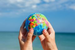 Woman holding globe of the Earth on a background of the sea. Concept ecology, peace,, save the planet Earth stock photo