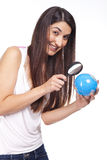 Woman holding a globe and using a magnifying glass Royalty Free Stock Image