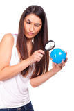 Woman holding a globe and using a magnifying glass Stock Photos