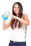 Woman holding a globe and using a magnifying glass Stock Photo